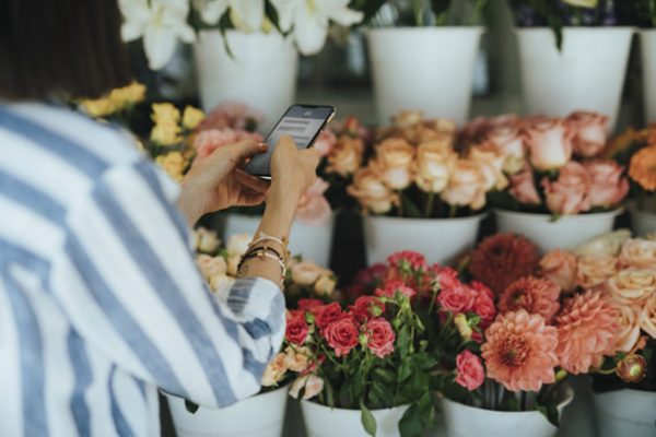 Woman messaging in a flower shop